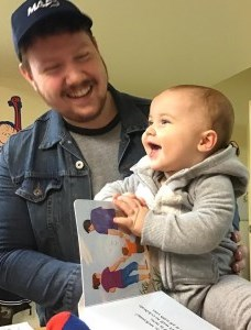 father holding his smiling baby who is holding a board book